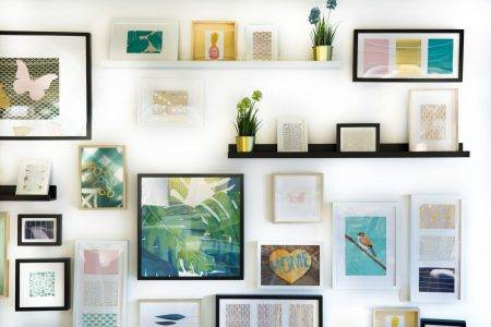 framed artwork and shelves neatly arranged on a white wall