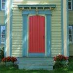 a red front door on a green and blue house